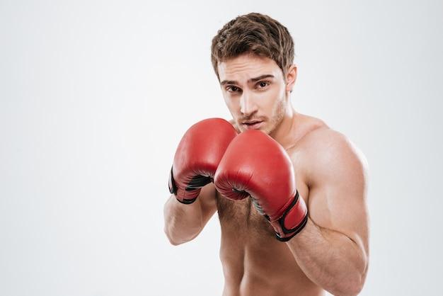 Портрет привлекательного боксера молодого человека стоя над белой стеной.