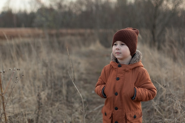 Портрет привлекательного молодого человека, улыбающегося и смотрящего в камеру в поле