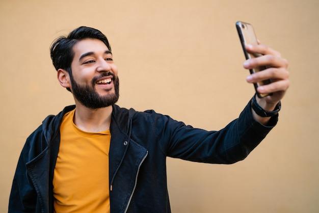黄色の壁に彼のmophile電話でselfiesを取っている魅力的な若い男の肖像画。技術コンセプト。