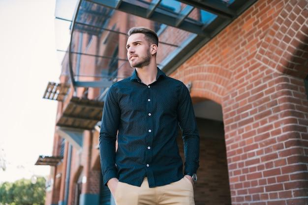 カジュアルな服を着て、屋外に立っている魅力的な若い男の肖像画