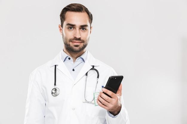 Портрет привлекательного молодого врача со стетоскопом, работающего в клинике и держащего мобильный телефон, изолированного над белой стеной