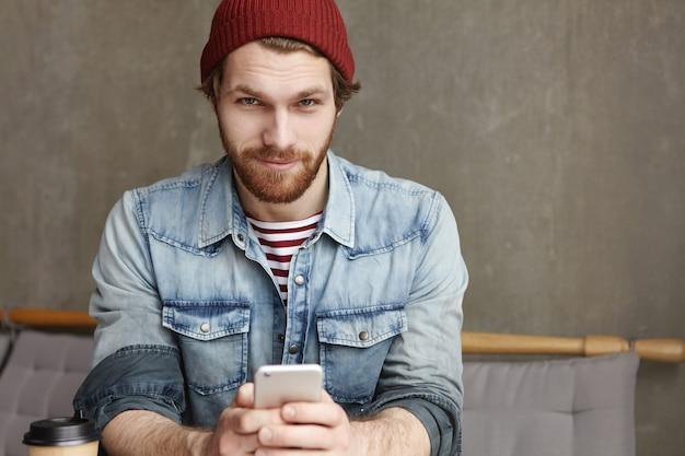 Портрет привлекательной молодой студентки с густой бородой в шляпе и джинсовой куртке