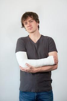 흰 벽에 그의 팔에 석고 캐스팅 매력적인 젊은 화가 남자의 초상화