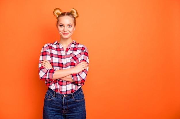 Портрет привлекательной молодой женщины, одетой в клетчатую рубашку, изолированную на оранжевом