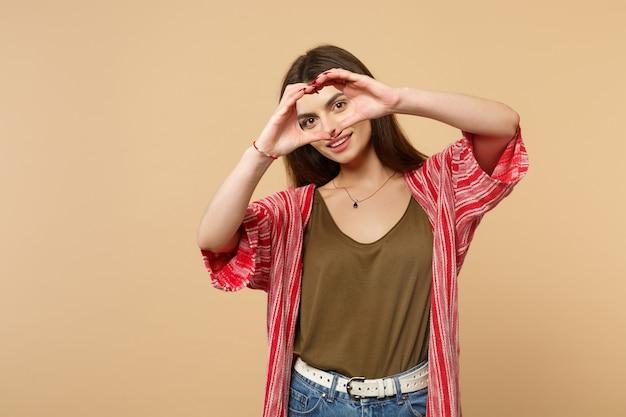 Портрет привлекательной молодой женщины в повседневной одежде, показывающей сердце формы с руками, изолированными на пастельных бежевых стенах в студии. концепция образа жизни искренние эмоции людей. копируйте пространство для копирования.