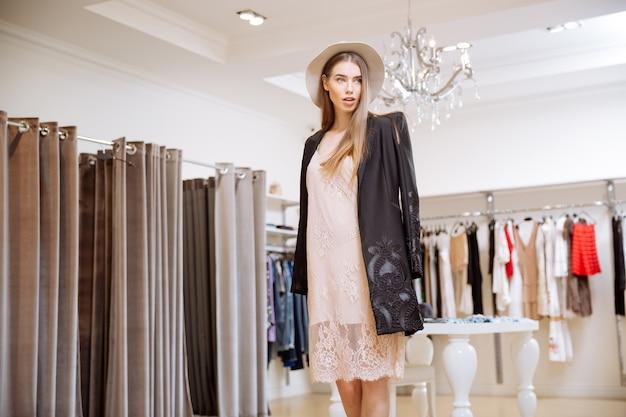 衣料品店に立っている帽子をかぶった魅力的な若い女性の肖像画