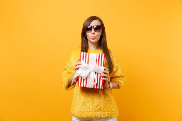 ギフトと赤い箱を保持している唇を吹く赤い眼鏡の魅力的な若い女性の肖像画、明るい黄色の背景で隔離のプレゼント。人々の誠実な感情、ライフスタイルのコンセプト。広告エリア。