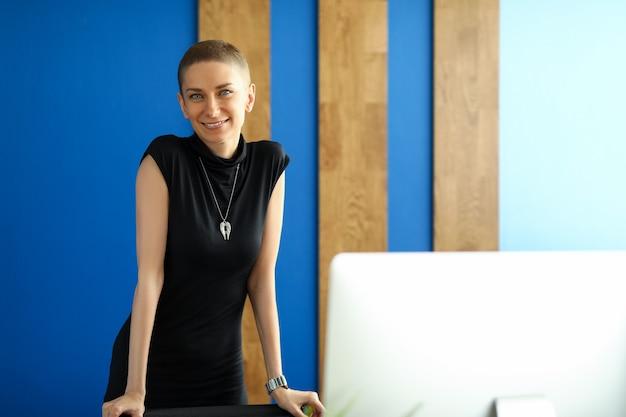 個人的なオフィスでポーズをとって魅力的な若い女性の肖像画。長い黒のドレスを着ている笑顔の陽気な女性。
