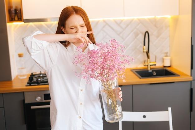 집에서 향기로운 석고꽃다발 냄새를 맡고 재채기를 하는 매력적인 젊은 여성의 초상화