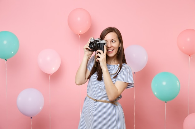 파란 드레스를 입은 매력적인 젊은 여성의 초상화는 화려한 공기 풍선과 함께 분홍색 배경에 복고풍 빈티지 사진 카메라로 사진을 찍습니다. 생일 휴일 파티 사람들은 진심 어린 감정 개념입니다.