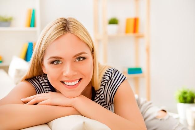 家で休んでいる晴れやかな笑顔と魅力的な若い女性の肖像画