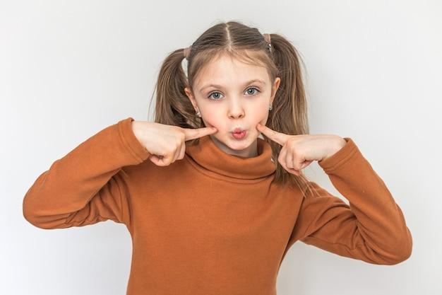 장난 꾸러기 어린 소녀의 초상화는 흰색 배경에 그녀의 뺨에 그녀의 손가락을 잡고 재미있는 얼굴을 만든다