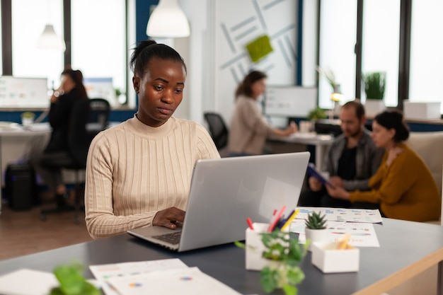 Портрет аутентичной африканской деловой женщины, читающей электронную почту на ноутбуке, сидя за столом в загруженном стартовом офисе, в то время как разнообразная команда анализирует статистические данные