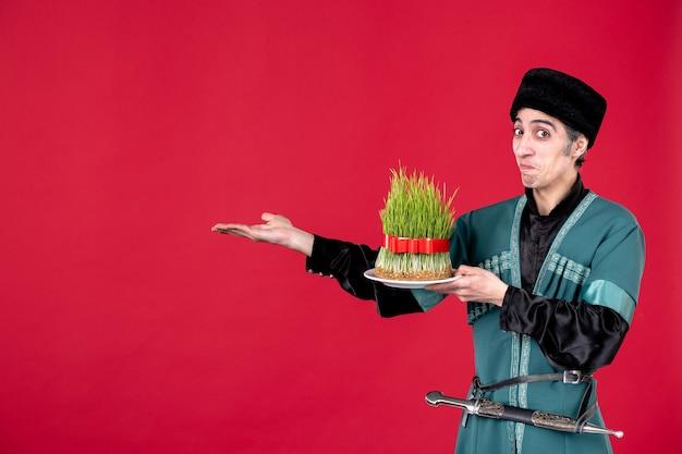 赤い民族の春のダンサーの休日にセメニを与える伝統的な衣装でアゼルバイジャンの男の肖像画