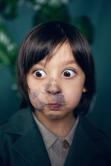 Портрет мальчика смазывают лицо торта