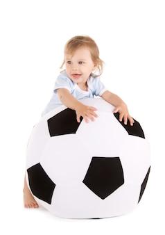 흰 벽에 축구 공과 아기의 초상화