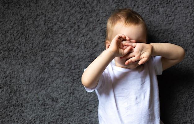 女の赤ちゃんの肖像画は、目に見えないか、見たくないように手を閉じて、カーペットの上に仰向けに横たわっているいないいないばあを楽しんでいます