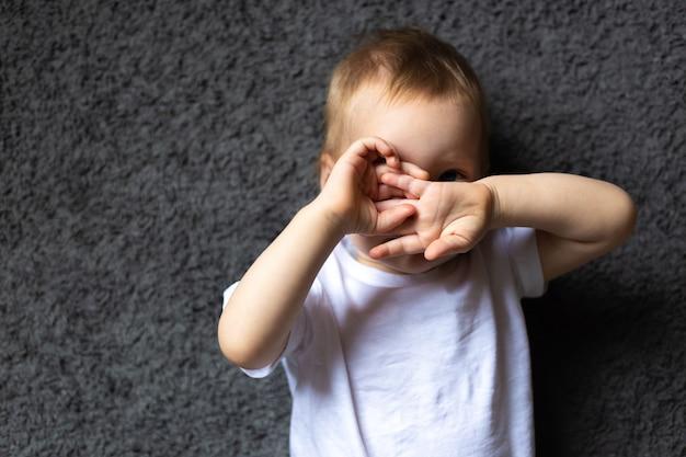 女の赤ちゃんの肖像画は、目に見えないか、見たくないために手で目を閉じました
