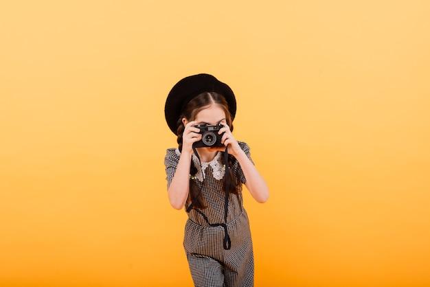 黄色の背景で隔離の写真カメラを保持している女の赤ちゃんの肖像画