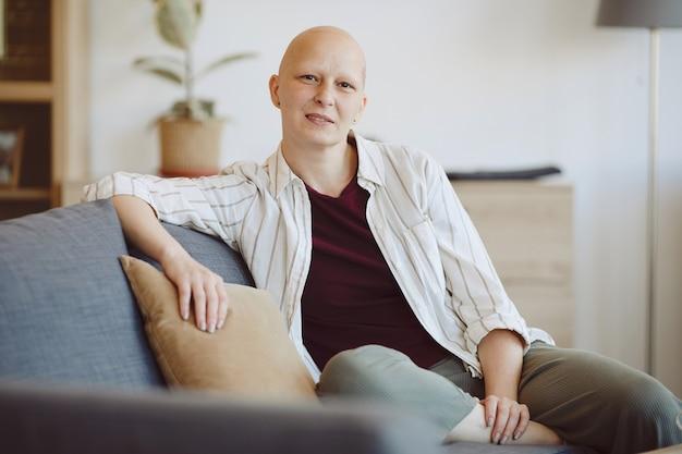 Портрет лысой взрослой женщины, смотрящей в камеру, сидя на диване в современном домашнем интерьере, осознание алопеции и рака, копировальное пространство