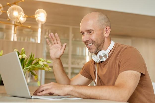 Портрет лысого зрелого мужчины, улыбающегося и махающего перед камерой во время разговора по видеочату через ноутбук в современном домашнем интерьере