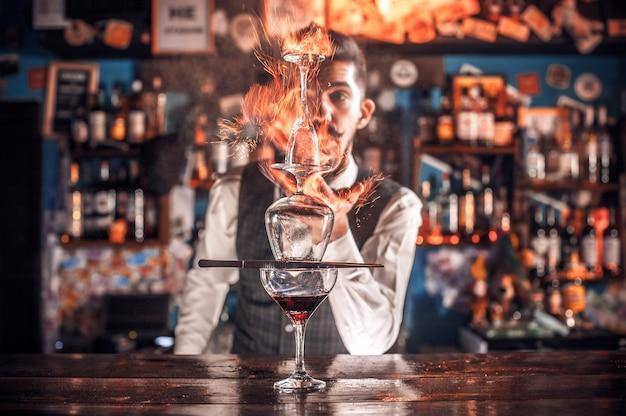 Портрет бармена, украшающего красочную смесь, стоя возле барной стойки в пабе