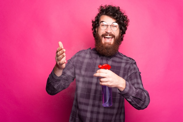 Портрет бородатого и кудрявого мужчины, улыбающегося и распыляющего дезинфицирующее средство для рук