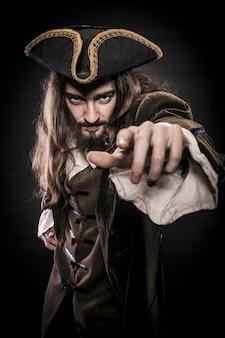 ひげを生やした髪の毛のある海賊がビューアーを指している、浅いdofの肖像画
