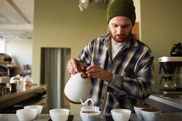 Портрет бородатого бариста, разливающего кофе по чашкам в ряд, стоя в баре, копия пространства