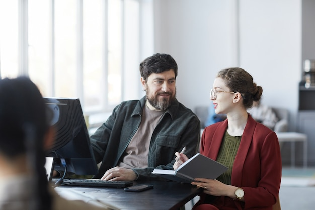 Портрет бородатого бизнес-менеджера разговаривает с коллегой во время встречи за столом в белом интерьере офиса