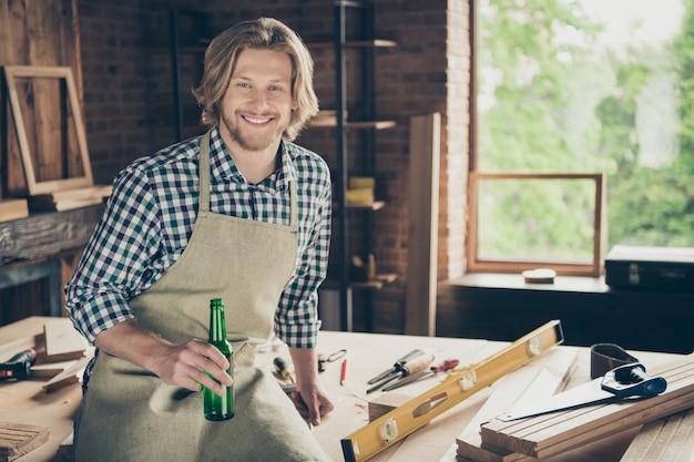 Портрет бородатого мастера позирует в своей деревянной мастерской с пивом