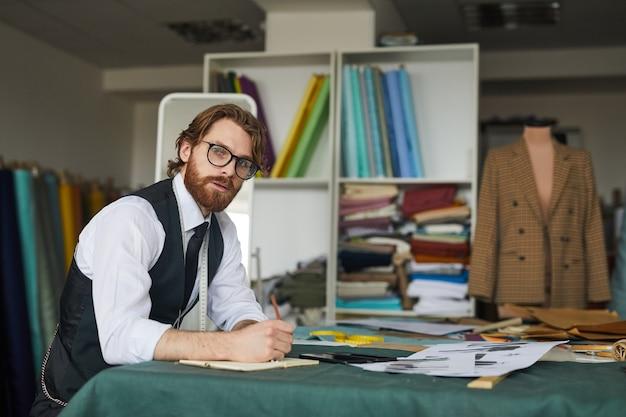 Портрет бородатого дизайнера в очках, сидящего за столом и планирующего свою работу в ателье
