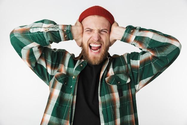 Портрет бородатого парня в шляпе и клетчатой рубашке, кричащего и закрывающего уши, стоя изолированно на белом фоне