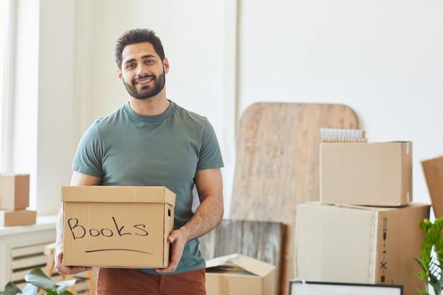 本と笑顔でボックスを保持しているひげを生やした幸せな男の肖像画