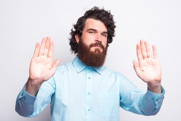 Портрет бородатого мужчины в непринужденной обстановке, делая стоп-жест, социальная дистанция