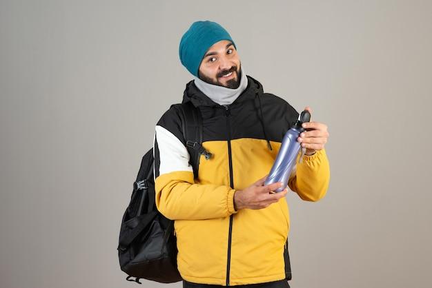 Портрет бородатого мужчины в теплой шляпе, стоящего и держащего бутылку с водой у серой стены.