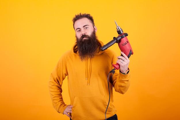 노란색 후드티를 입은 수염 난 남자의 초상화는 빨간색 전원 드릴을 들고 노란색 배경 위에 있는 카메라를 보고 있습니다. 남성 노동자입니다. 자신감 있는 남자.