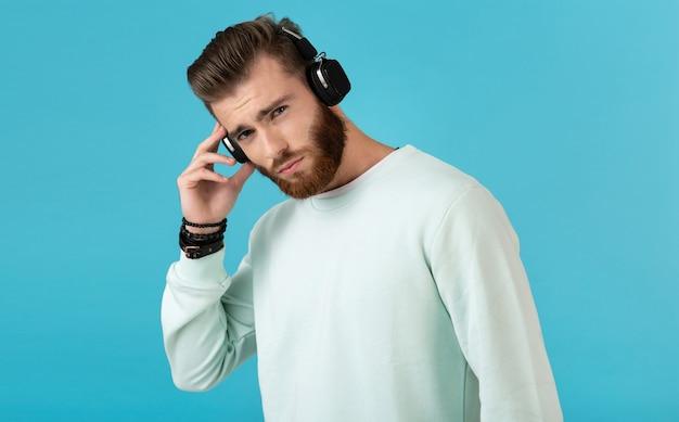 Портрет бородатого мужчины, слушающего музыку в беспроводных наушниках на синем