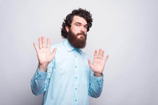 Портрет бородатого мужчины, делающего стоп-жест, социальная дистанция, правила пандемии.