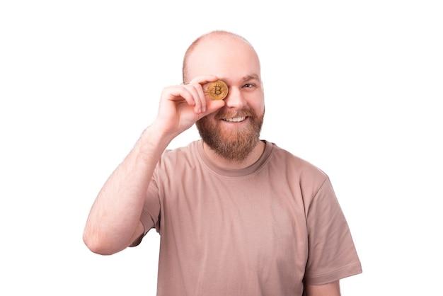 Портрет бородатого мужчины, улыбающегося и держащего биткойн над глазом на белой стене