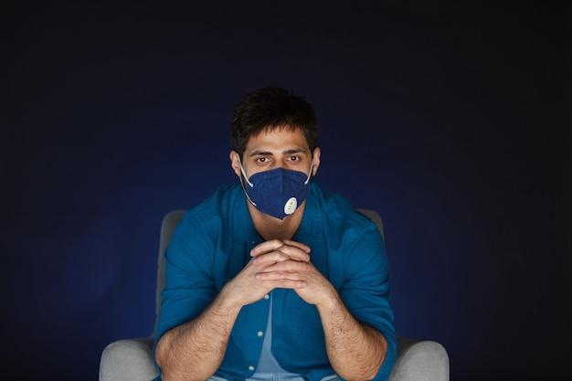 検疫で自宅で映画を見ながらマスクを身に着けているひげを生やした男の肖像画