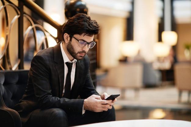 호텔 라운지에서 기다리는 동안 스마트폰을 사용하는 수염난 중동 사업가의 초상화, 복사 공간