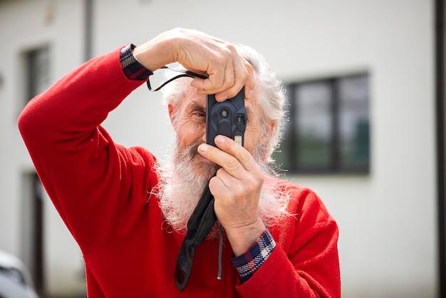写真を撮る古いカメラとひげを生やした年配の男性写真家の肖像画