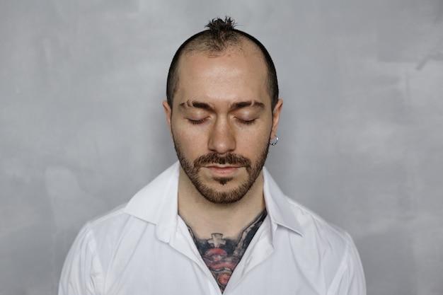 Портрет бородатого татуированного мужчины в белой рубашке с закрытыми глазами
