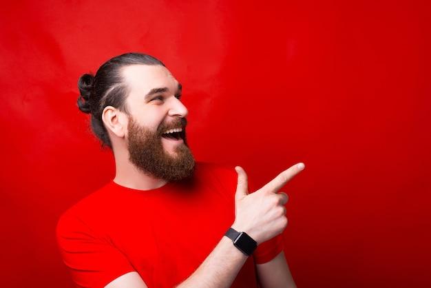 Портрет бородатого молодого человека, улыбающегося и указывающего на угол