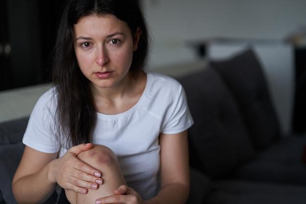 Портрет избитой женщины со слезами на лице и синяком на коленях сидит на диване.