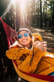 Beautifu女性の肖像画笑顔と森の森の公園でリラックスして自由なアウトドアレジャー活動をお楽しみください-高い木々とバックゴーンドの日光-屋外で陽気な女性