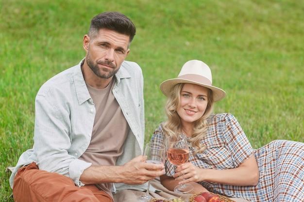 Портрет красивой взрослой пары, сидящей на зеленой траве, наслаждающейся пикником на открытом воздухе