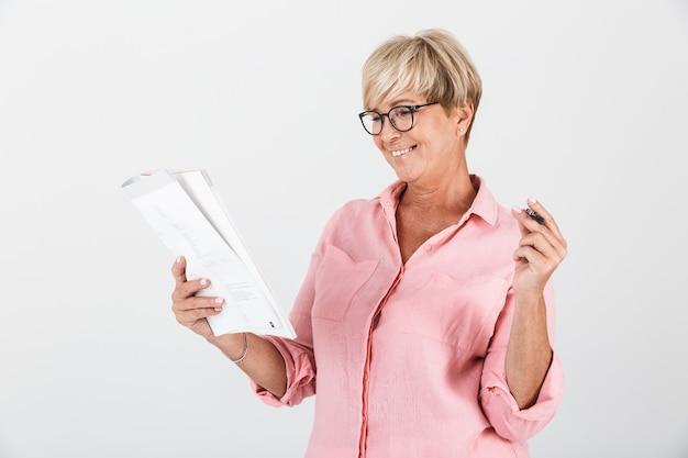 Портрет красивой взрослой женщины в очках, держащей учебную книгу и ручку, изолированную над белой стеной в студии