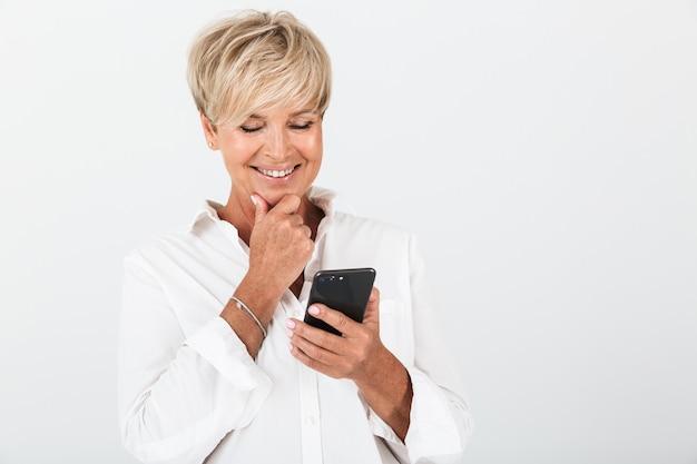 スタジオで白い壁の上に分離された携帯電話を笑顔で保持している短いブロンドの髪を持つ美しい大人の女性の肖像画